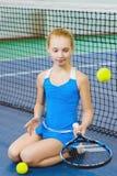 打网球和法庭上摆在室内的逗人喜爱的女孩 免版税库存图片