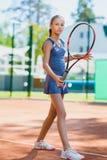 打网球和法庭上摆在室内的逗人喜爱的女孩 免版税库存照片