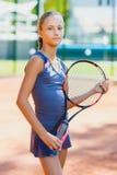 打网球和法庭上摆在室内的逗人喜爱的女孩 库存图片