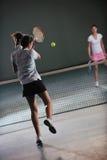 打网球比赛的女孩室内 免版税库存图片
