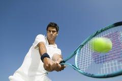 打网球的坚定的人反对天空 免版税库存照片