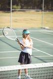 打网球的女孩在晴天期间 免版税图库摄影