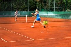 打网球的妇女户外 免版税库存照片