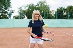 打网球的少妇拿着球拍 摆在蓝色体育礼服的网球场的白肤金发的女孩 库存照片