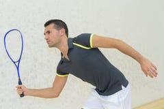 打网球的年轻人户内 免版税库存图片