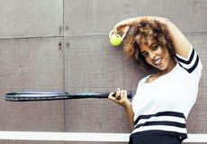 打网球的年轻时髦的美国黑人的女孩,炫耀健康l 免版税库存照片