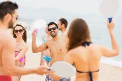 打网球的微笑的朋友在海滩 免版税库存照片