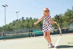 打网球的愉快的小女孩 库存照片