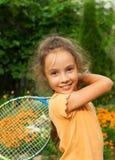 打网球的逗人喜爱的微笑的小女孩画象在夏天 图库摄影
