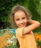 打网球的逗人喜爱的微笑的小女孩画象在夏天 库存图片