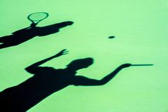 打网球的年轻夫妇 免版税库存图片