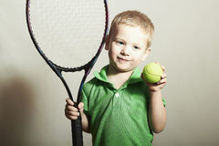 打网球的年轻男孩。体育孩子。有网球拍和球的孩子 免版税库存图片