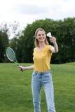 打羽毛球比赛在公园,夏令时概念的微笑的妇女 库存照片