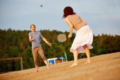 打羽毛球的夫妇在海滩 免版税库存照片