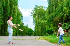 打羽毛球的母亲和儿子在公园 免版税图库摄影