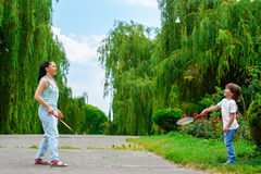 打羽毛球的母亲和儿子在公园 库存照片