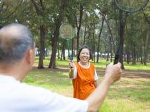 打羽毛球的资深夫妇或朋友 库存照片