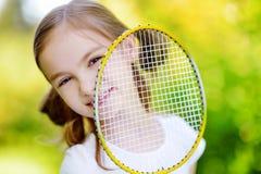 打羽毛球的逗人喜爱的小女孩户外 免版税图库摄影