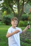 打羽毛球的逗人喜爱的男孩孩子夏天滑稽的画象在绿色公园 体育,健康生活方式 免版税库存照片