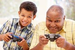 打计算机游戏的祖父和孙子 免版税库存图片