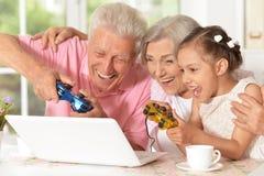 打计算机游戏的祖父母和孙女 免版税库存照片