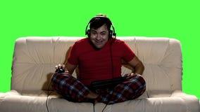 打计算机游戏的滑稽的人在家坐长沙发 股票视频
