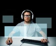 打计算机电子游戏的耳机的人 皇族释放例证