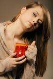 打赌的人 拿着杯子杯子热的饮料茶或咖啡的女孩 免版税库存照片