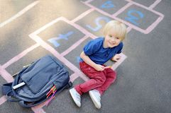 打跳房子比赛的逗人喜爱的白肤金发的男孩在有放置的袋子的学校以后近 库存图片