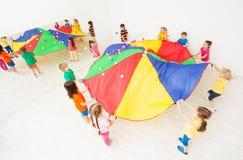 打降伞比赛的孩子在学校体育馆 免版税库存图片