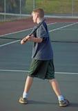 打青少年的网球的反手 免版税库存图片