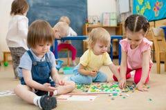 打马赛克比赛的孩子或孩子在幼儿园屋子里 免版税库存照片