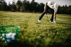 打高尔夫球与铁的近射从航路在日出 免版税库存照片