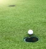 打高尔夫球与去陷井的球的领域孔 免版税库存图片