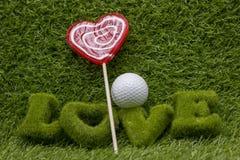 打高尔夫球充满在绿草的爱 免版税库存图片
