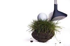打高尔夫球在草土块  免版税库存照片