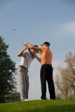 打高尔夫球帮助有他的摇摆的专家年轻人 免版税库存图片