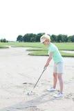 打高尔夫球的中年妇女在路线反对清楚的天空 库存照片