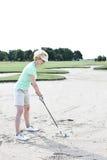 打高尔夫球的中年妇女在路线反对清楚的天空 库存图片