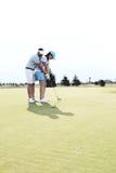 打高尔夫球的全长夫妇在路线反对清楚的天空 图库摄影