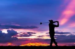 打高尔夫球的剪影高尔夫球运动员在美好的日落 库存照片
