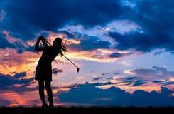 打高尔夫球的剪影高尔夫球运动员在美好的日落 免版税库存照片