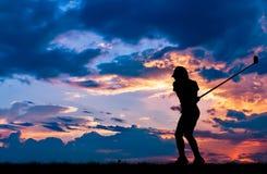 打高尔夫球的剪影高尔夫球运动员在美好的日落 免版税图库摄影