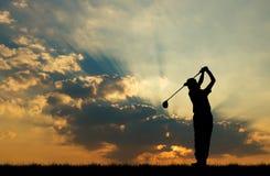 打高尔夫球的剪影高尔夫球运动员在美好的日落 图库摄影