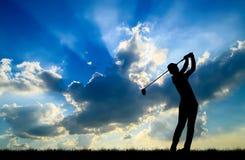 打高尔夫球的剪影高尔夫球运动员在美好的日落 免版税库存图片