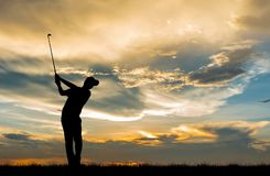 打高尔夫球的剪影高尔夫球运动员在美好的日落 库存图片