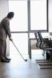 打高尔夫球的商人在他的办公室,拿着高尔夫俱乐部 库存照片
