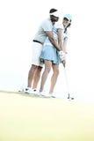 打高尔夫球的夫妇低角度视图在路线反对清楚的天空 库存图片