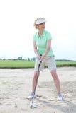 打高尔夫球的妇女在路线反对清楚的天空 库存图片