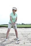 打高尔夫球的妇女在路线反对清楚的天空 免版税库存图片